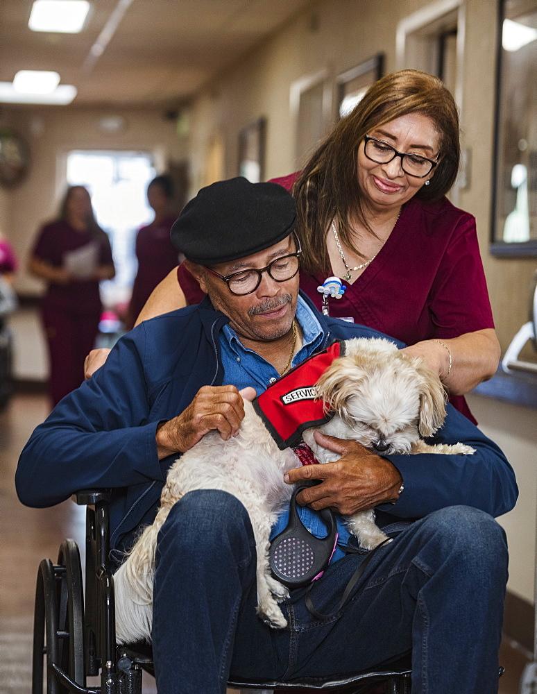 Smiling nurse pushing senior man holding dog in wheelchair