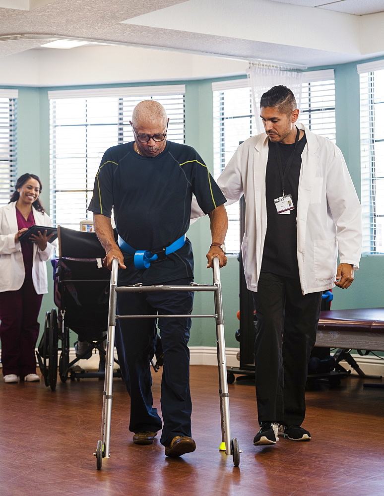 Doctor helping senior man use walking frame