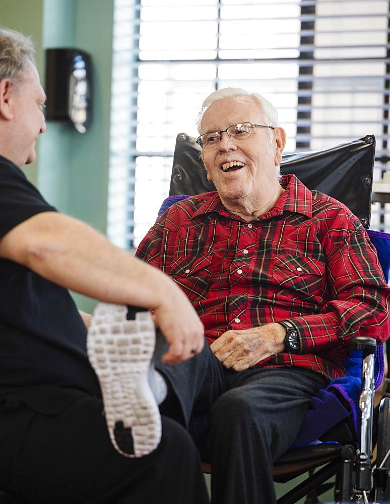 Nurse holding smiling senior man's foot in wheelchair