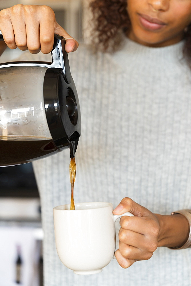 Woman pouring cup of coffee