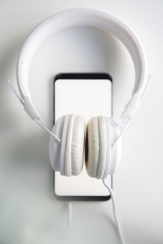 White headphones connected to smart phone