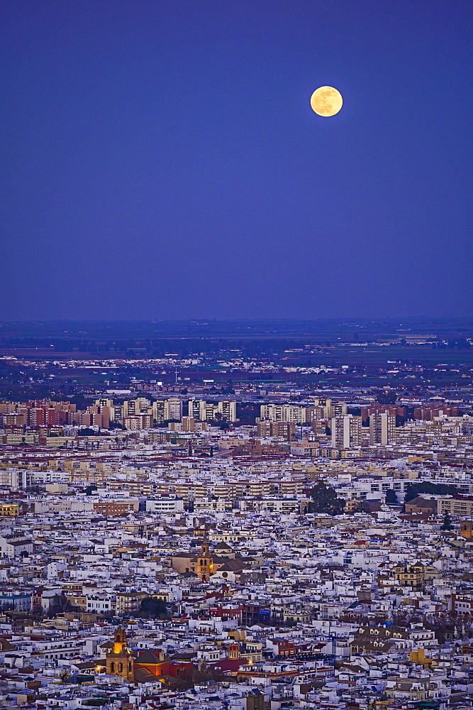 Spain, Andalusia, Seville, Moonrise over cityscape