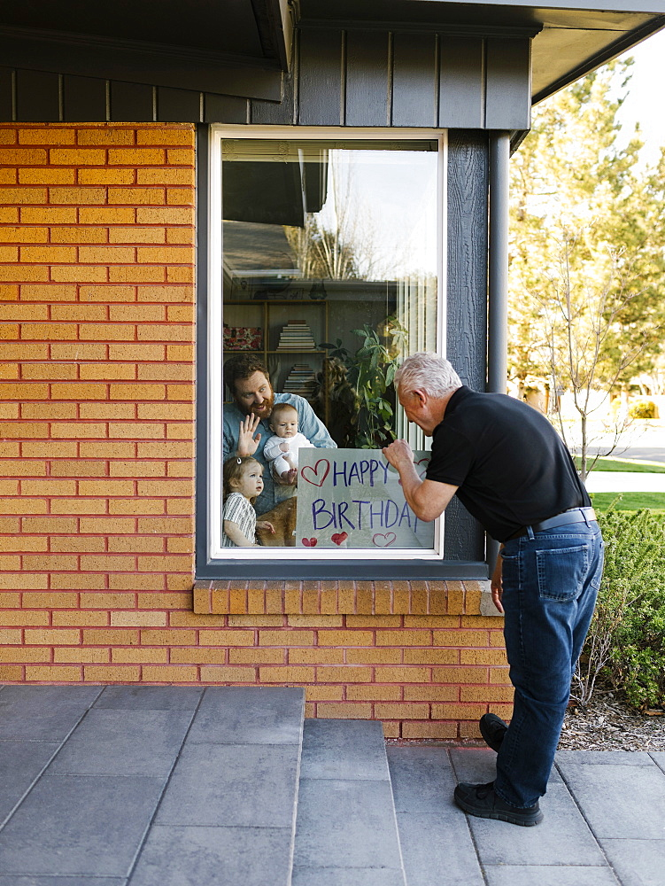 Grandfather visiting family with grandchildren (2-3 months, 2-3) through window