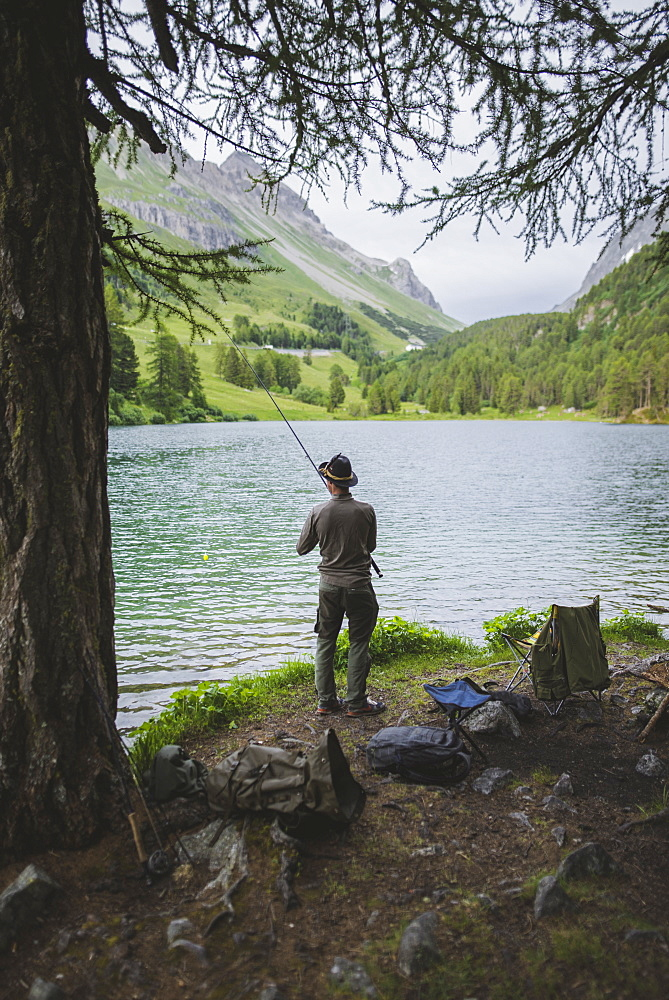 Switzerland, Bravuogn, Palpuognasee, Young man fishing in Palpuognasee lake in Swiss Alps