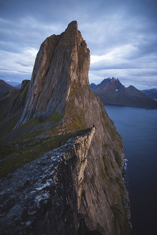 Norway, Senja, Man sitting on cliff edge near?Segla?mountain