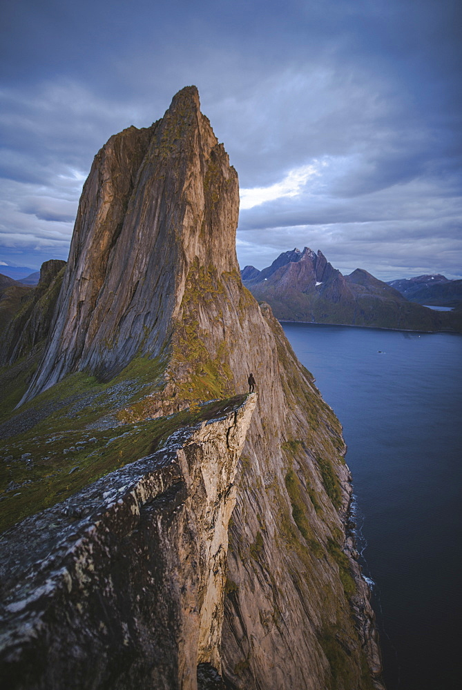 Norway, Senja, Man standing on cliff edge near Segla mountain