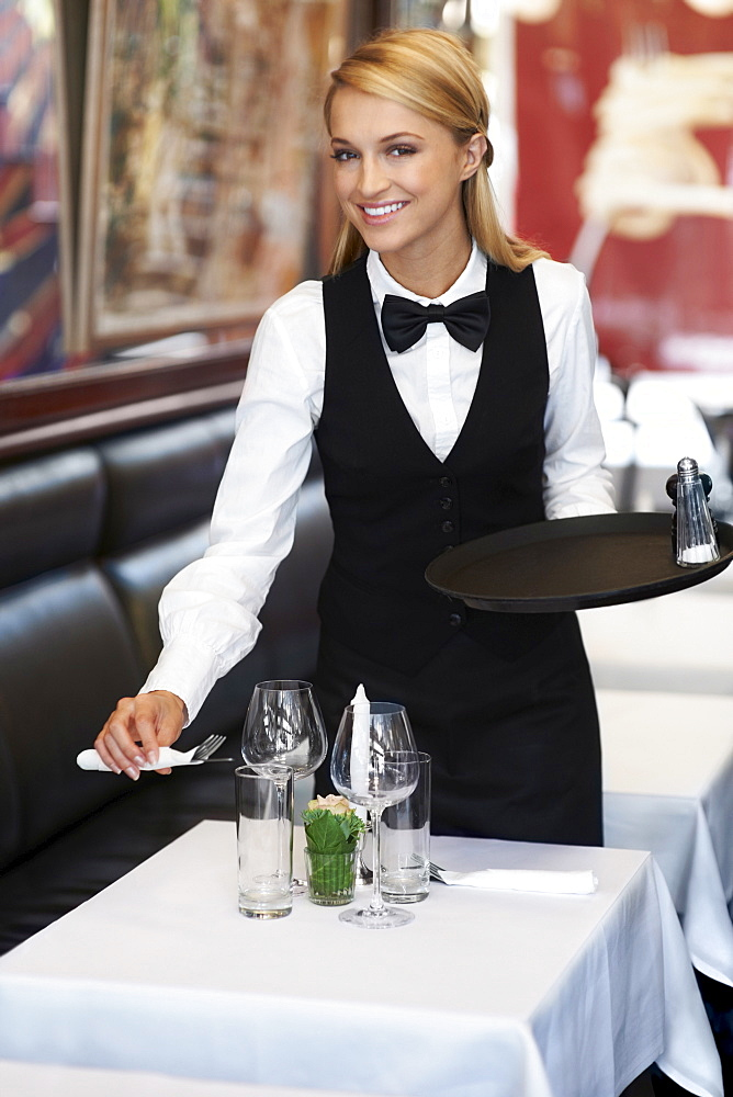 Portrait of young waitress setting table