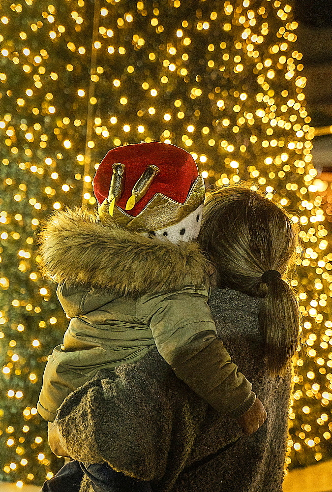 Mother and son watching illuminated Christmas tree