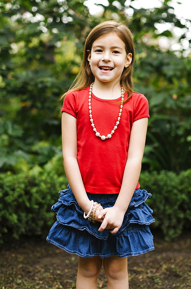 USA, California, Orange County, Portrait of smiling girl (6-7) wearing bead necklace