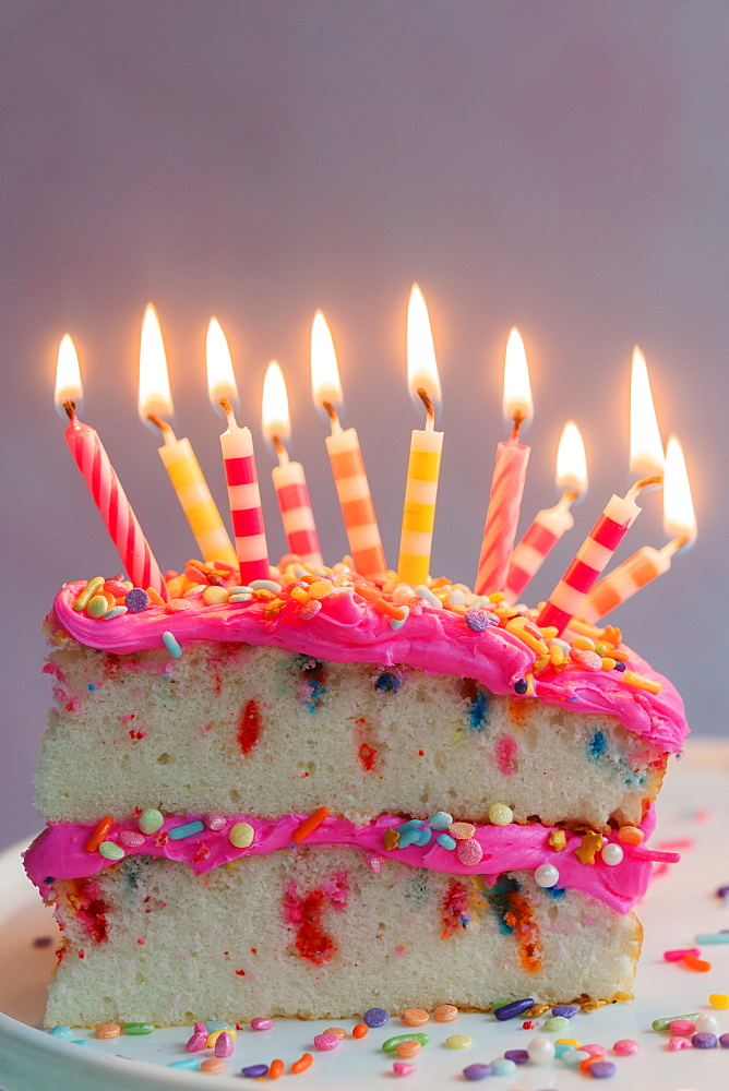 Slice of birthday cake with lit candles