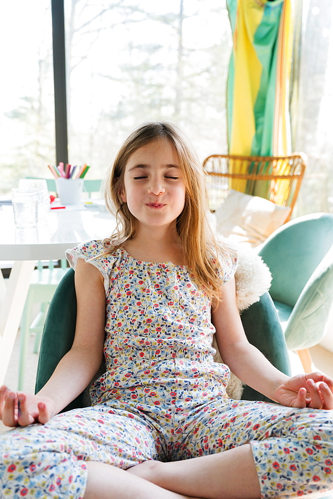 Girl (6-7) meditating at home