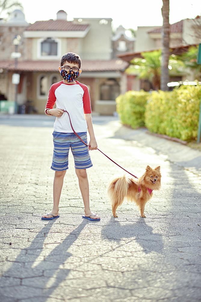 Mexico, Zapopan, Boy with face mask walking dog