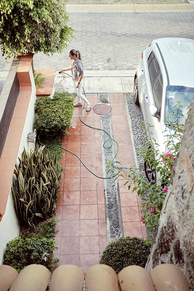 Mexico, Zapopan, Woman watering plants in driveway