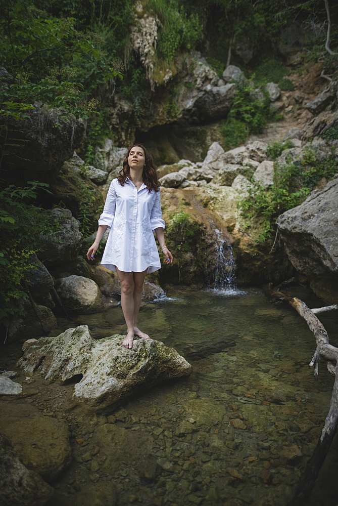 Ukraine, Crimea, Young woman standing on rock near waterfall
