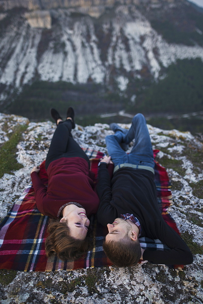 Ukraine, Crimea, Young couple lying down at plaid near canyon