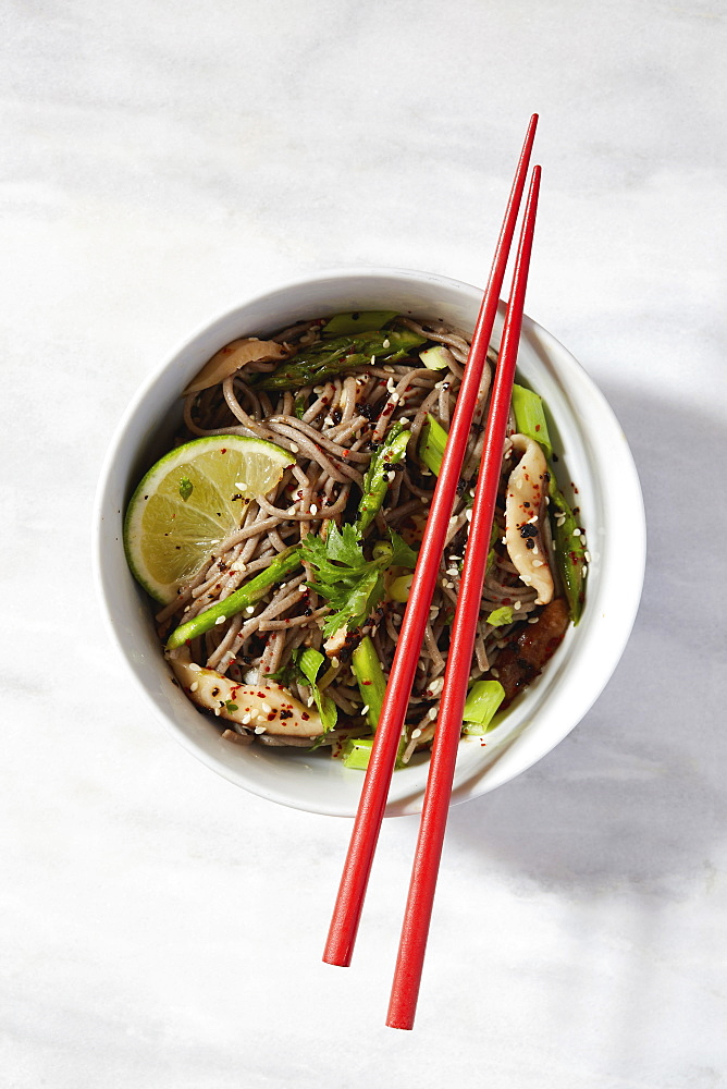 Asian meal in bowl with chopsticks