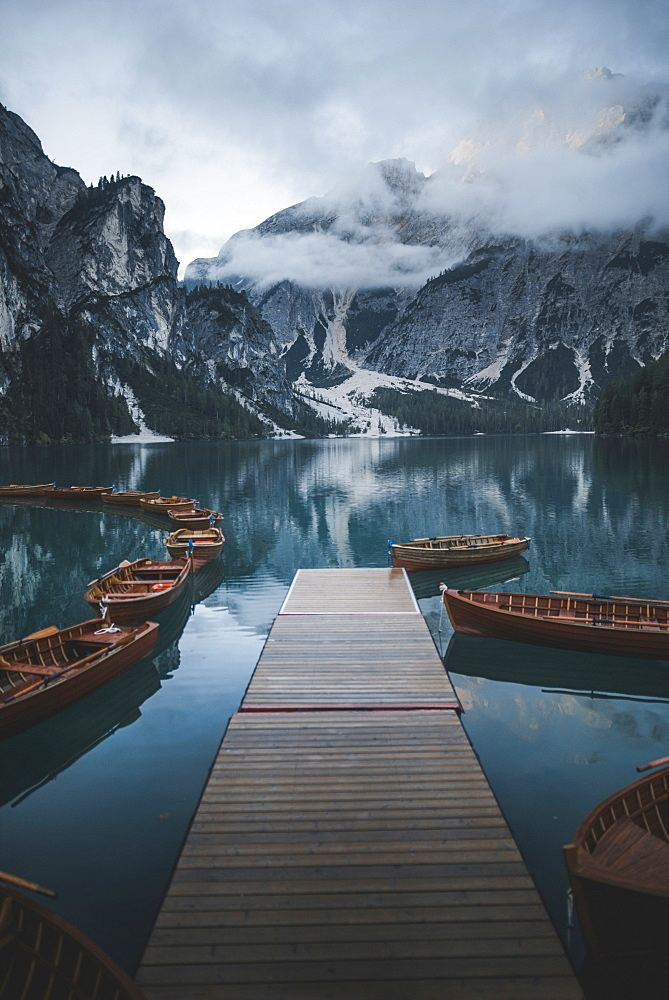 Italy, Wooden boats moored by pier at Pragser Wildsee in Dolomites