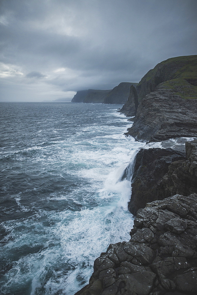 Denmark, Faroe Islands, Sorvagur, Rocky sea coast with storm clouds