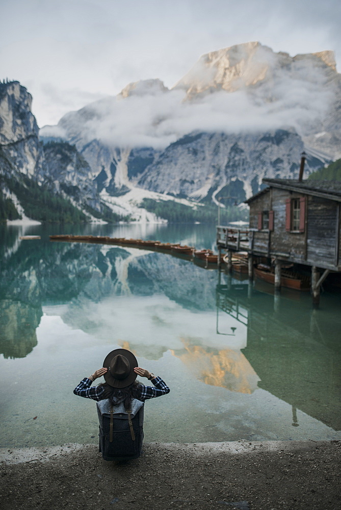 Italy, Woman sitting by Pragser Wildsee in Dolomites