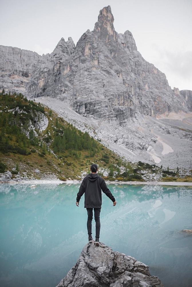 Italy, South Tyrol, Cortina d Ampezzo, lake Sorapis, Man standing on rock looking at lake - 1178-30410