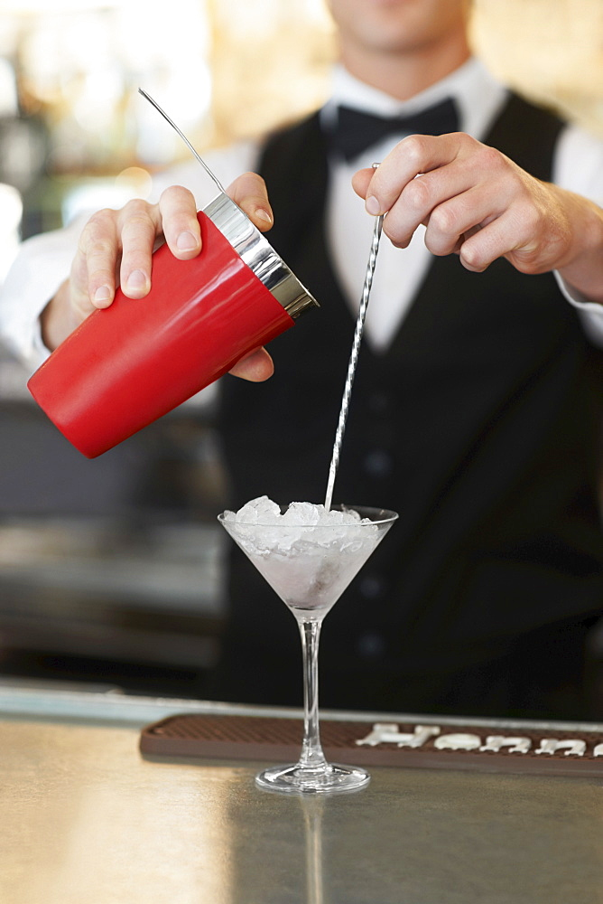 Young bartender pouring cocktail