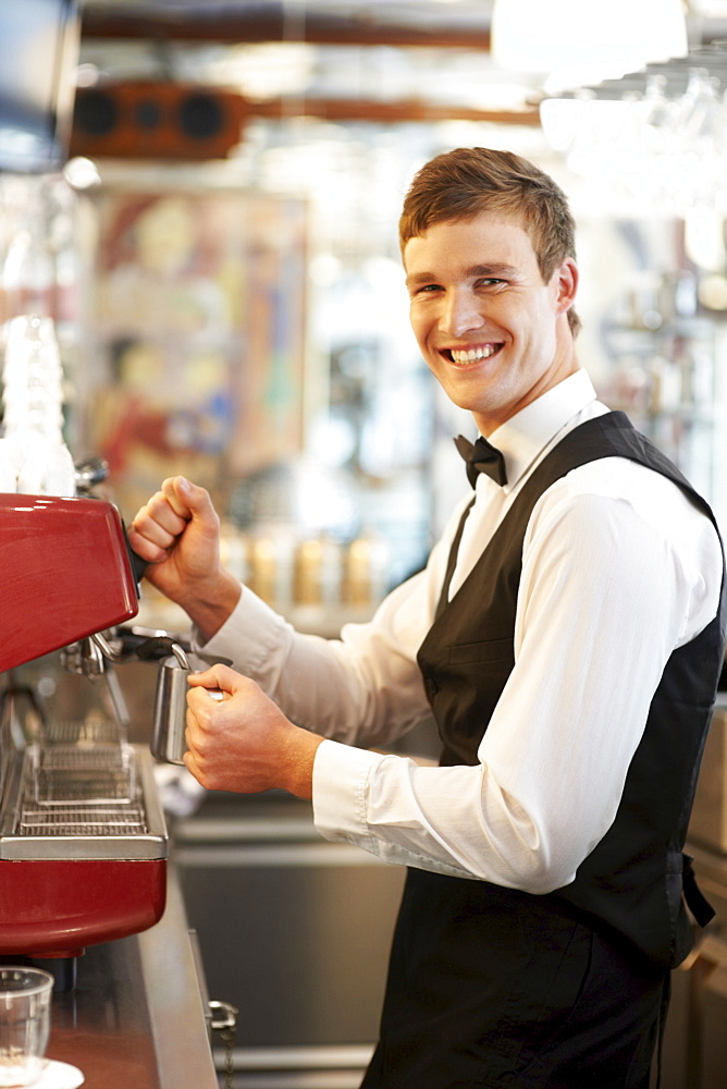 Portrait of barista standing by coffee maker