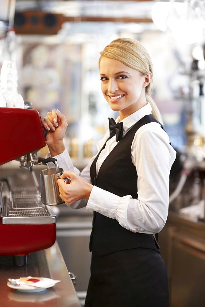 Female barista steaming milk