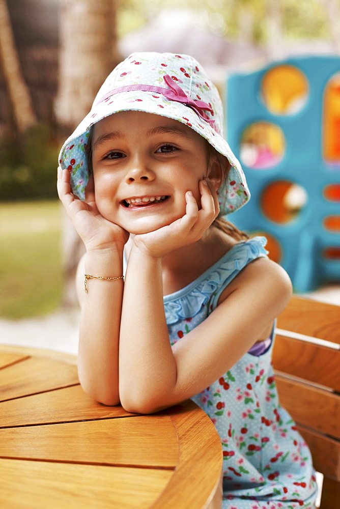 Portrait of smiling girl (6-7) sitting at table