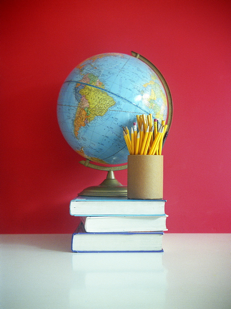Still life of books, pencils, and globe