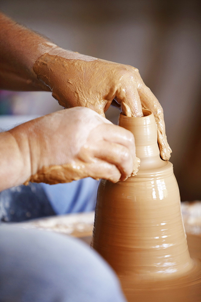 Hands working with clay on potter's wheel