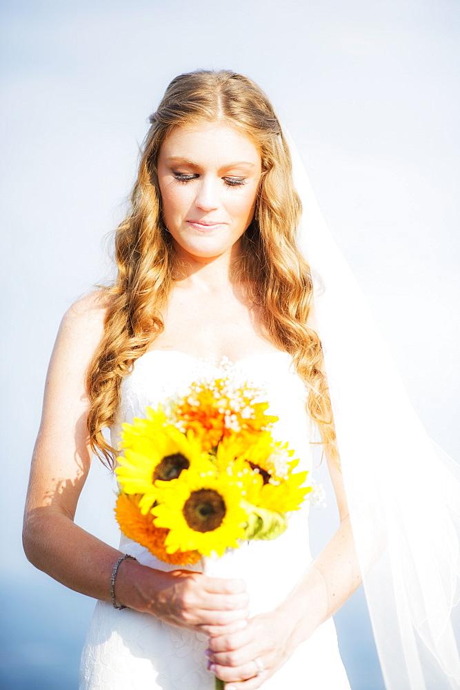 Portrait of bride holding sunflower bouquet