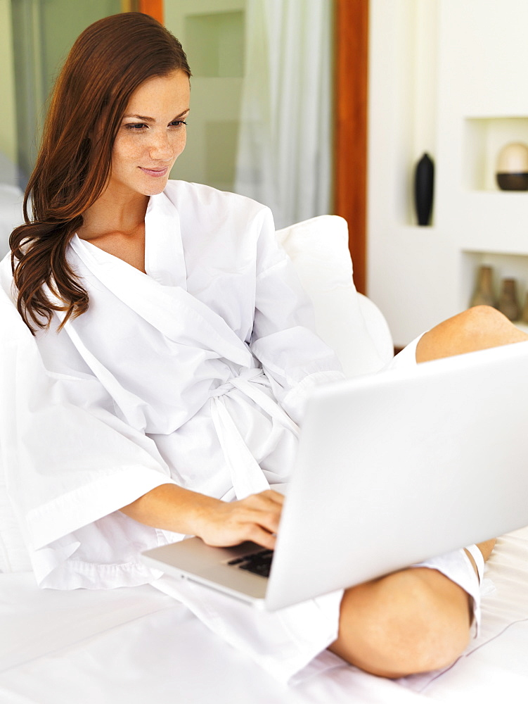 Woman using laptop while sitting on bed