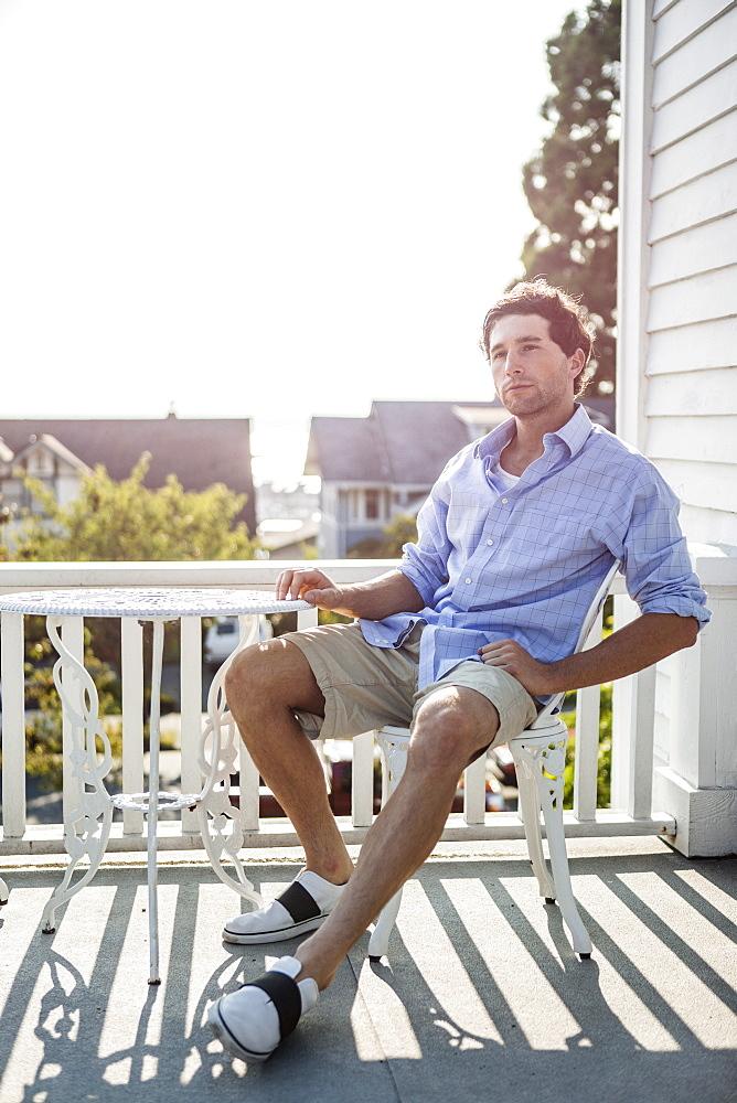 Portrait of young man relaxing on balcony, USA, Washington, Everett