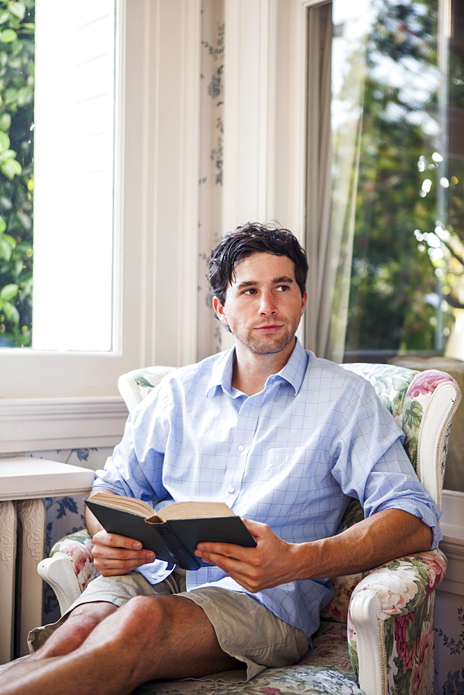 Portrait of young man relaxing with book