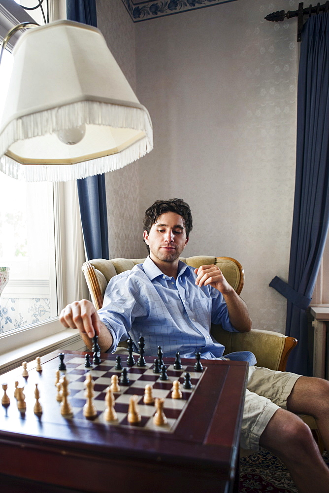 Portrait of young man playing chess