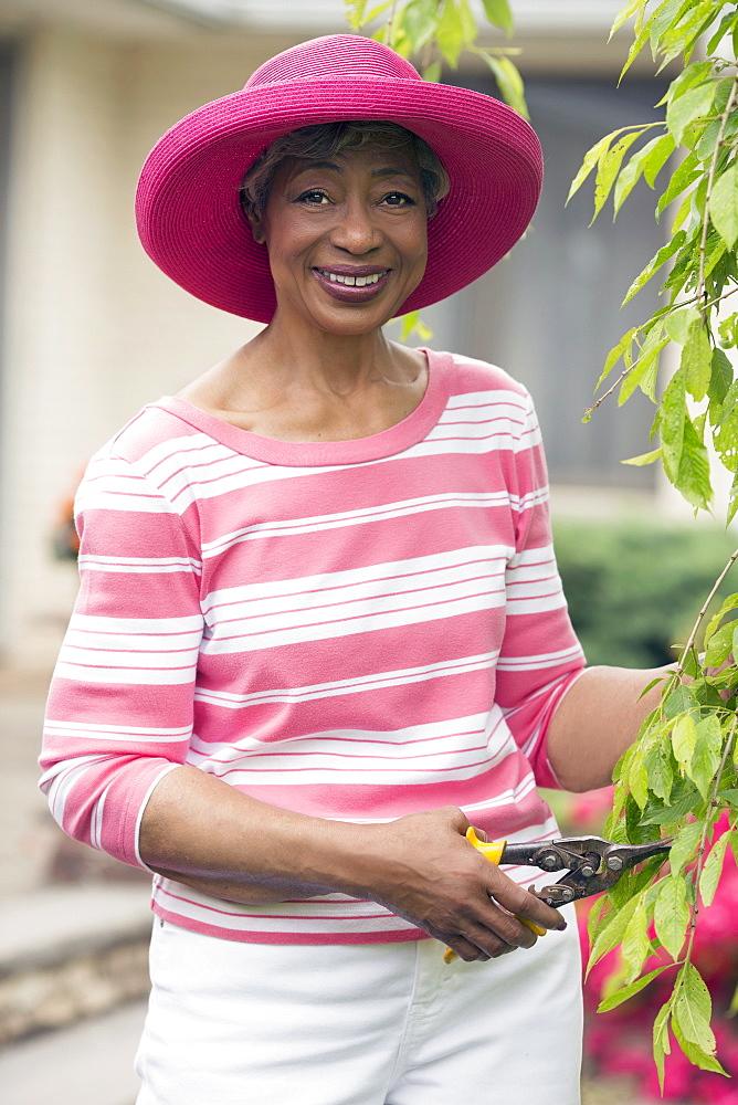Portrait of senior woman pruning branch