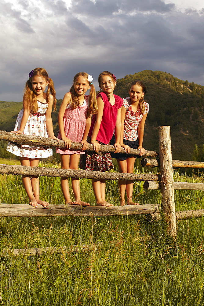 Four girlfriends (6-7, 8-9, 10-11) standing on wooden fence in grass, USA, Colorado