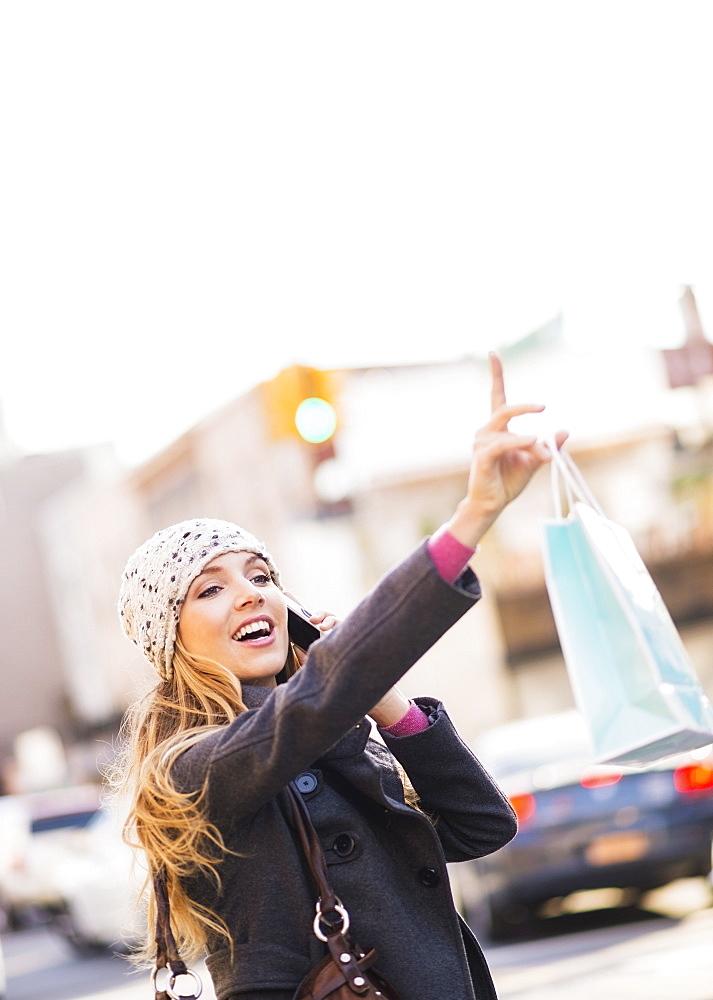 Portrait of blond woman hailing cab, USA, New York City, Brooklyn, Williamsburg