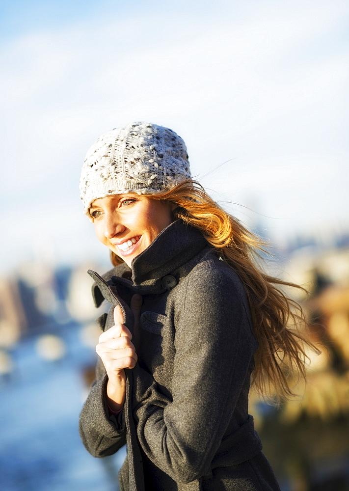 Portrait of cheerful woman in overcoat in autumn, USA, New York City, Brooklyn, Williamsburg