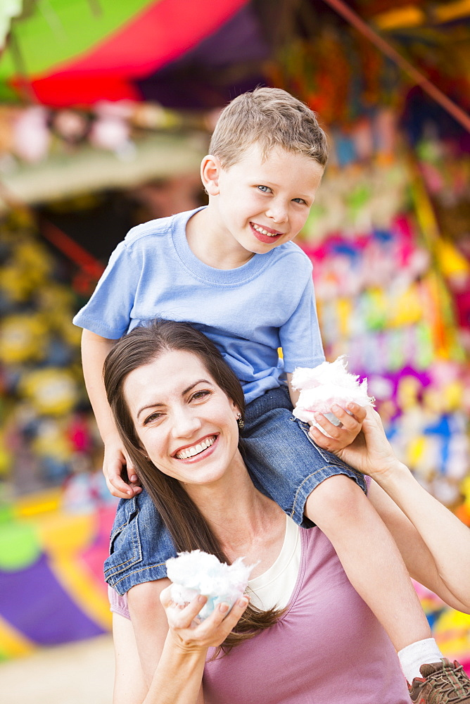 Happy mother with son (4-5) in amusement park eating cotton candy, USA, Utah, Salt Lake City