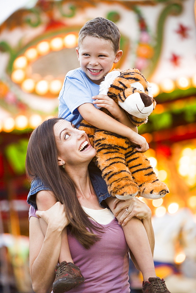 Mother giving her son (4-5) piggyback ride in amusement park, USA, Utah, Salt Lake City