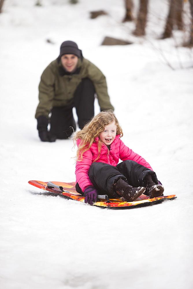 Young man sledding with girl (4-5)