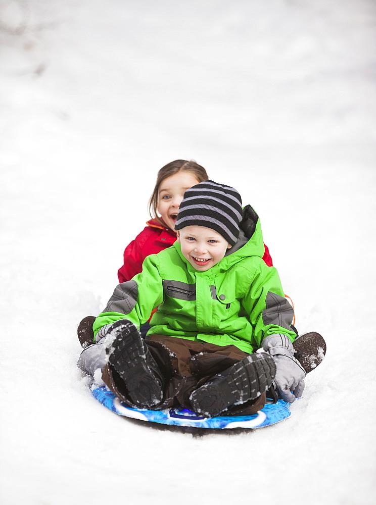 Portrait of two sledding children (2-3, 4-5)