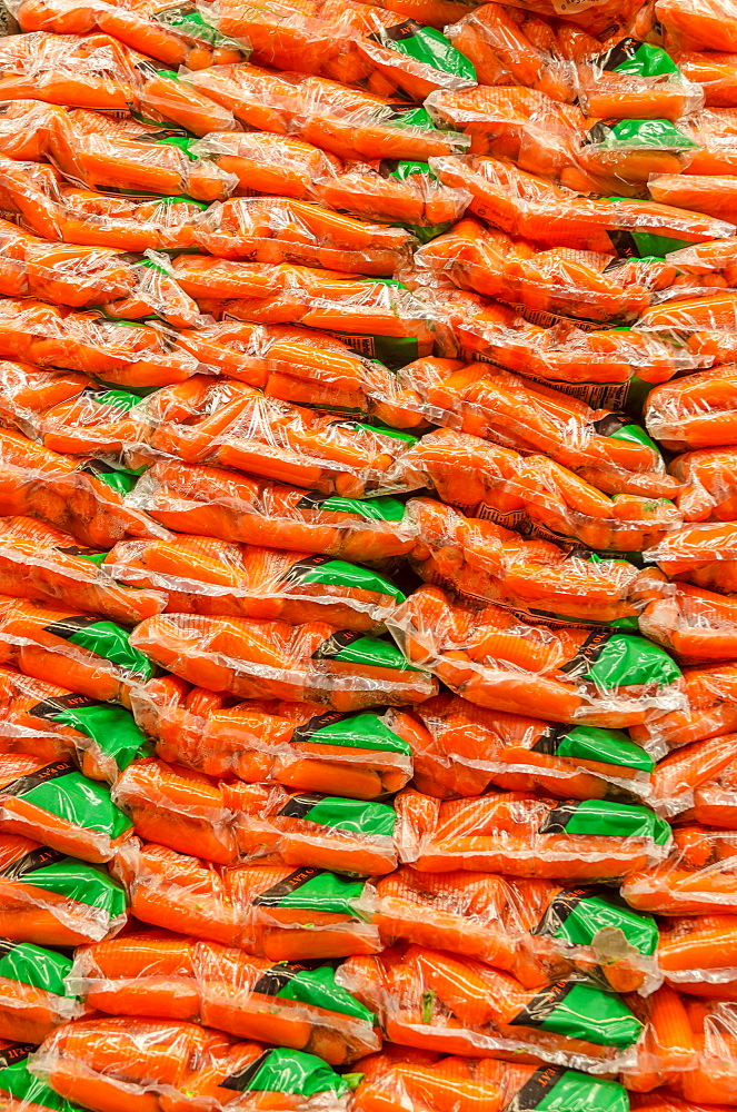 Stack of plastic bags packed with carrots