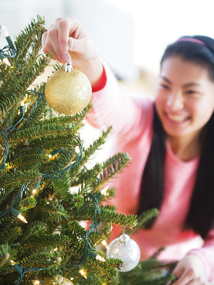 Teenage girl ( 16-17 years) decorating Christmas tree