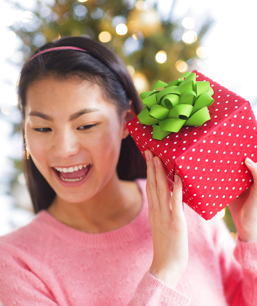 Front view of teenage girl ( 16-17 years) holding Christmas gift
