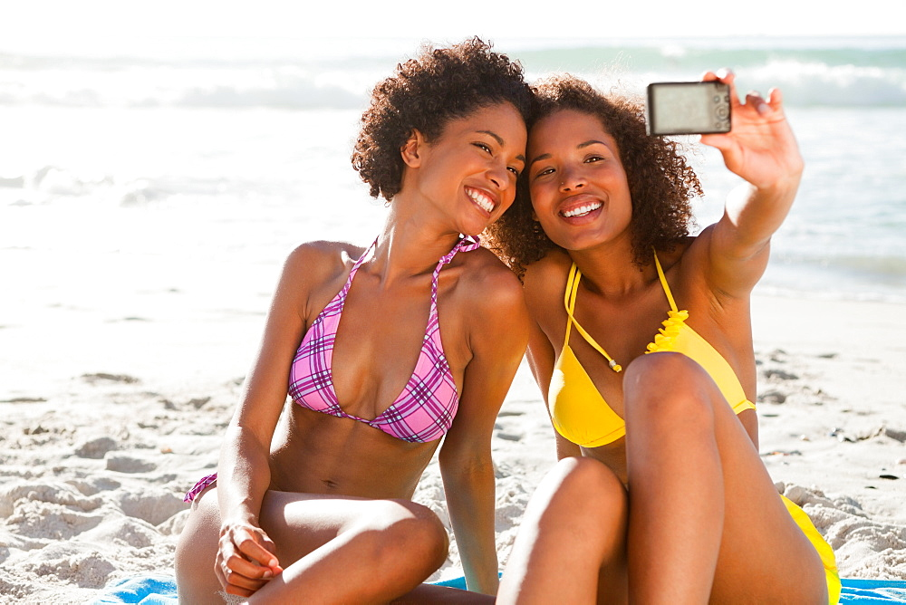 Young smiling women photographing themselves with a digital camera