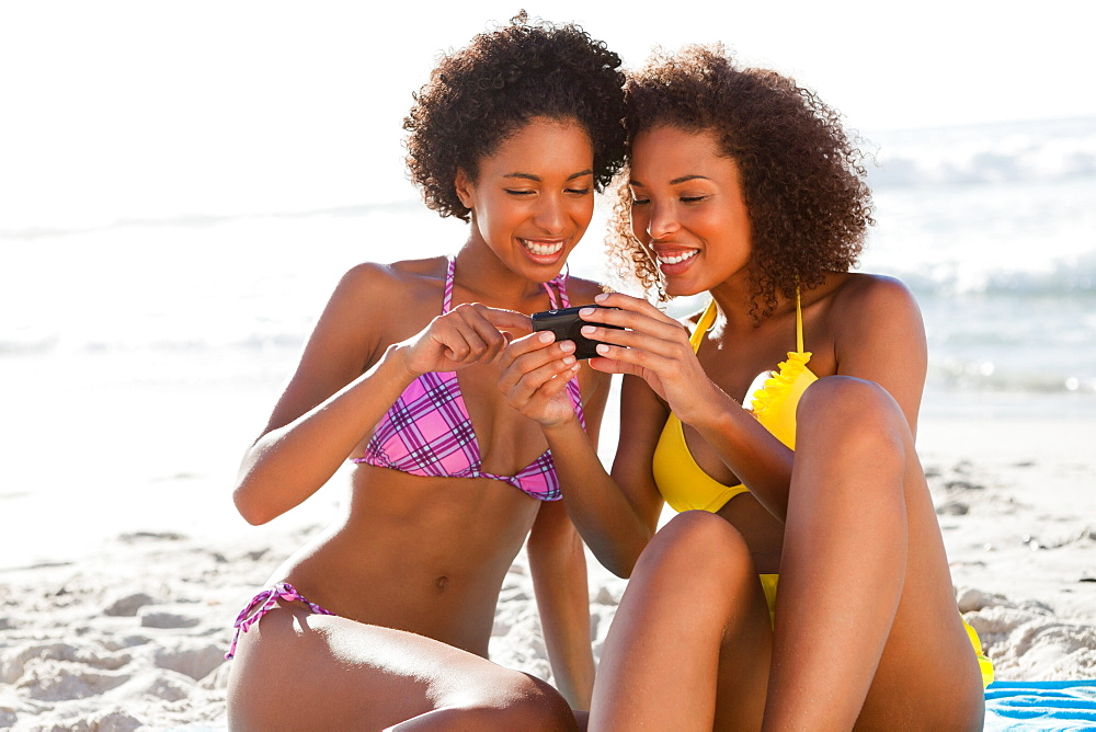 Young beautiful women in swimsuits looking at a digital camera