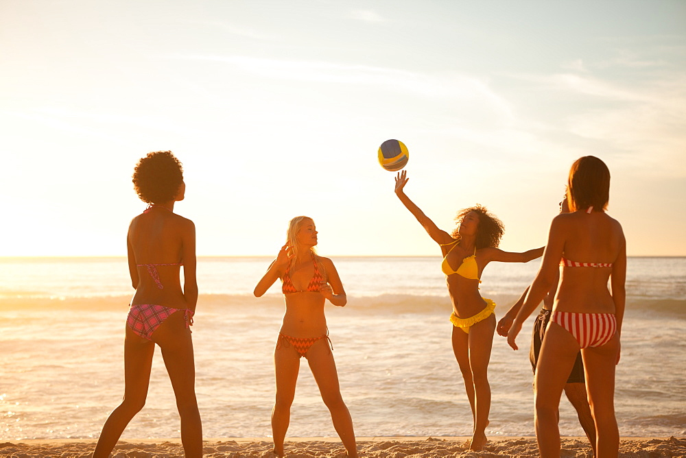 Young women playing with a beach ball in front of the sea - 1120-1044
