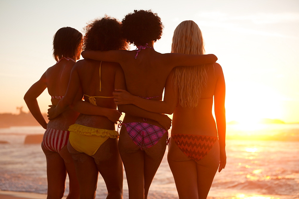Young attractive women holding each other in front of the ocean
